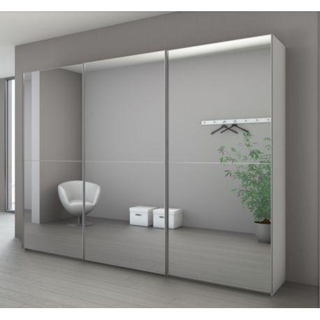 Armoire avec portes miroir dans lesquelles se reflète la pièce.