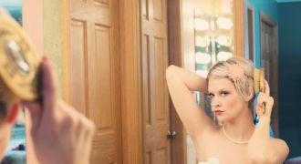 Jeune femme qui se regarde dans un miroir.