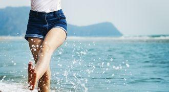 Femme en short qui marche dans la mer.
