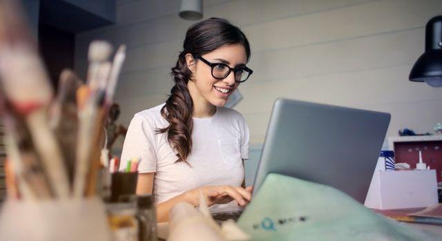 Jeune femme devant son ordinateur en train de configurer son placard sur mesure.